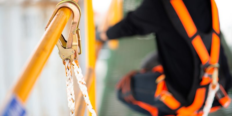 Construction worker wearing safety harness and safety line worki